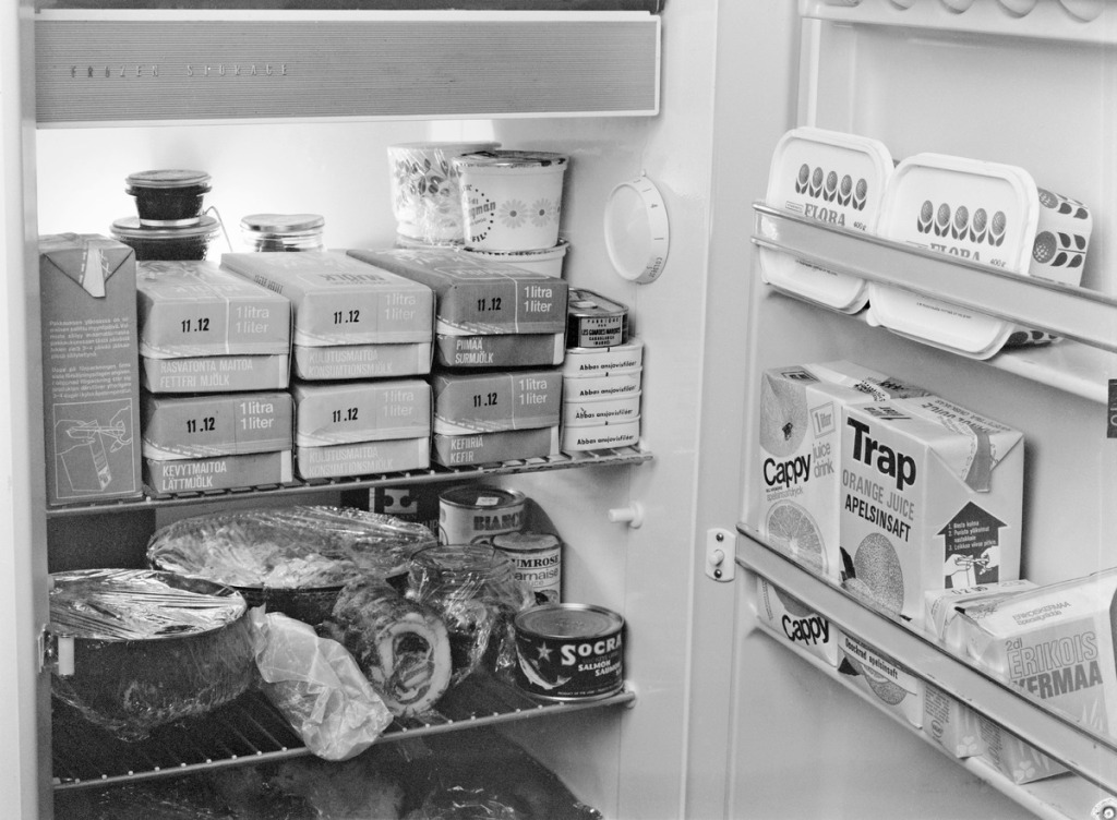 Aukinainen jääkaappi, jonka sisällä paljon erilaisia elintarvikkeita, kuten maitotuotteita ja margariinia. Mustavalkokuva.