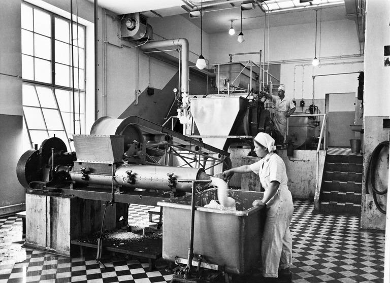 Teollisuushalli, jonka keskellä suuri teollisuuskone. Koneen oikealla puolella nainen. Mustavalkokuva.